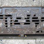 Grille d'évacuation des eaux présentant des lieux et figures emblématiques de Kobe