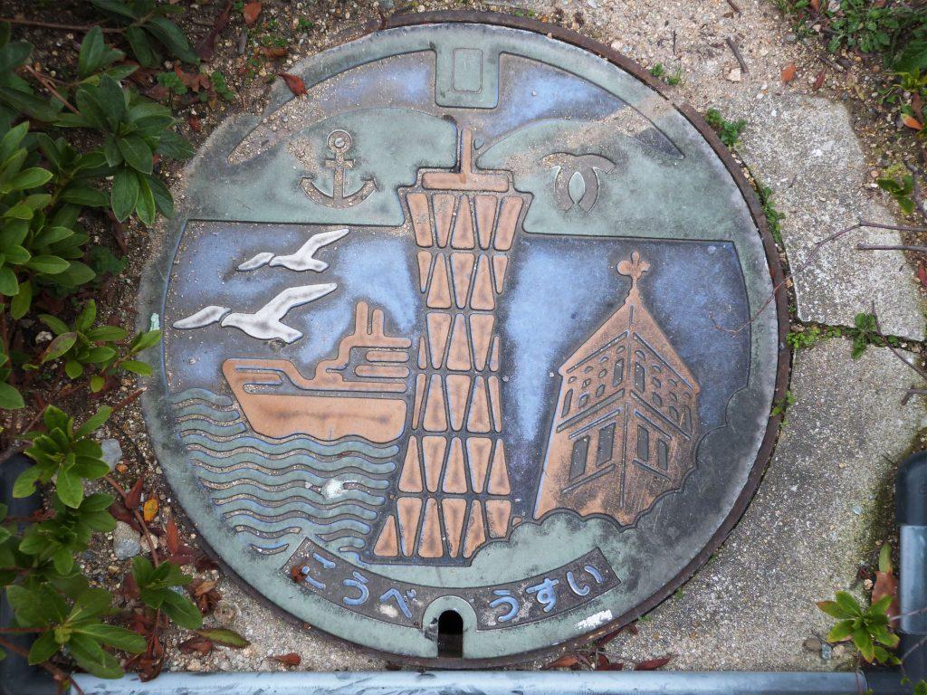 Couvercle de regard de chaussée de Kobe ; on où voit les collines de la ville et ses emblèmes, un paquebot, la tour du port et la girouette
