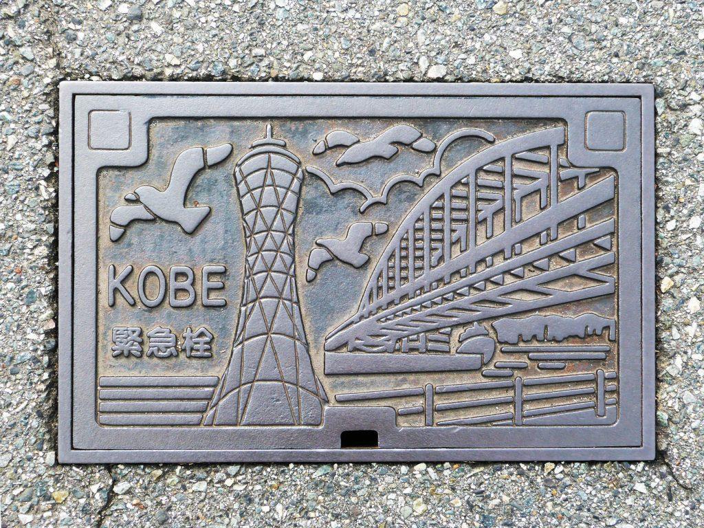 Plaque rectangulaire de la ville de Kobe sur laquelle sont représentées la tour du port et le grand pont ainsi que des mouettes