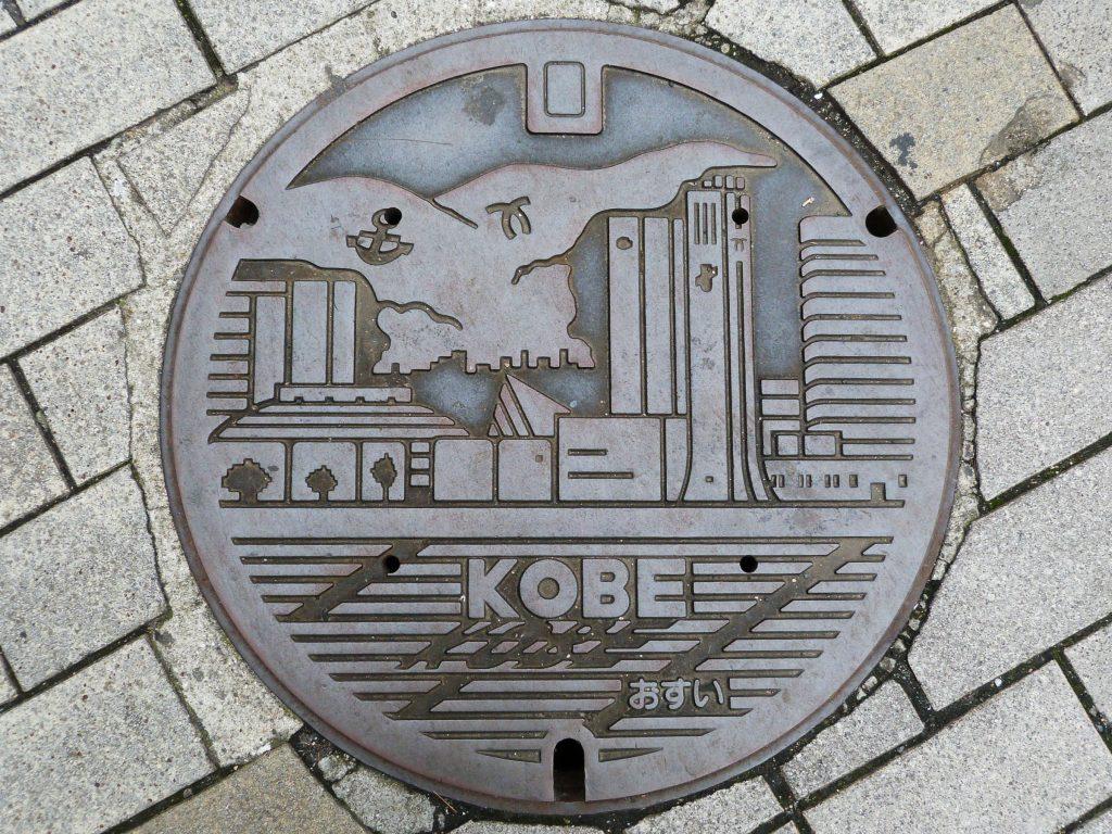 Plaque de regard de chaussée figurant une vue de la ville de Kobe depuis la mer