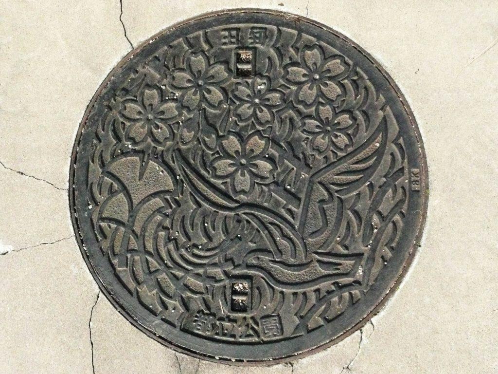 Plaque des parques municipaux de Tokyo ; des fleurs de cerisier, une mouette et des feuilles de ginko biloba y sont représentés