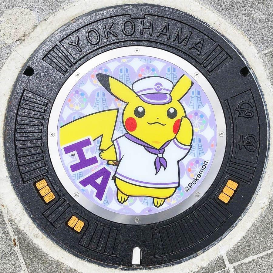 PokéPlak avec Pikachu matelot et le Yo de Yokohama sur un fond violet à motifs de grande roue et de tour