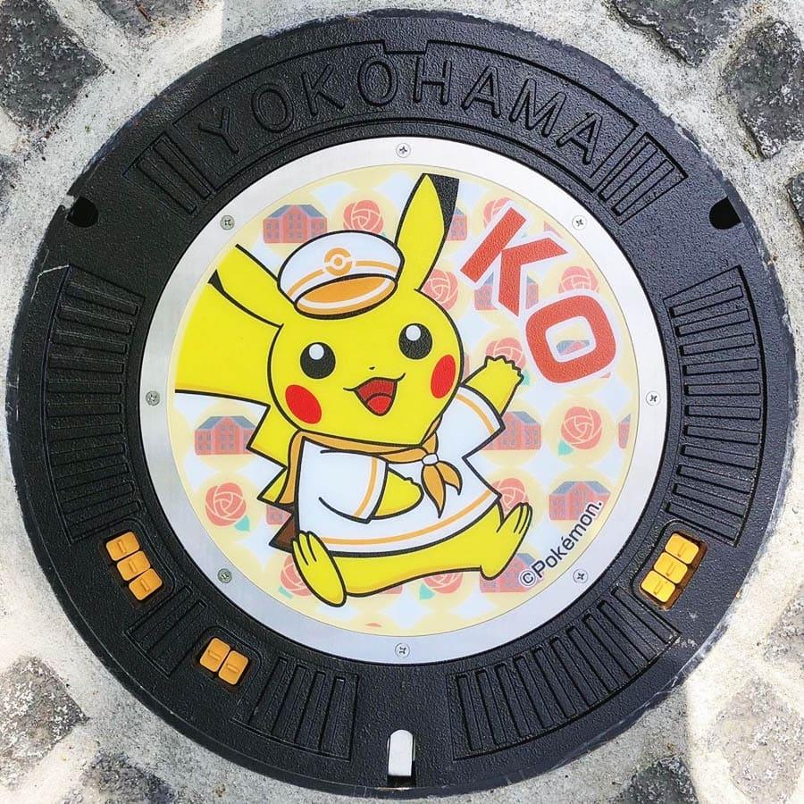 PokéPlak avec Pikachu matelot et le Yo de Yokohama sur un fond rouge à motifs de roses et d'entrepôts en briques