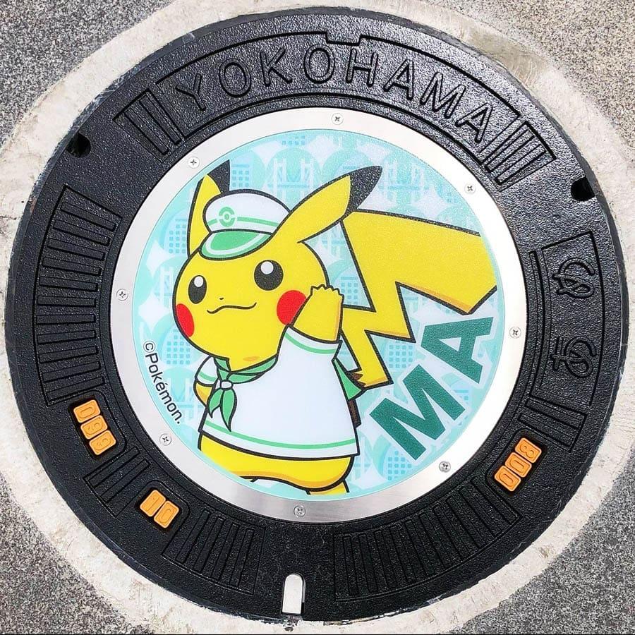 PokéPlak avec Pikachu matelot et le Yo de Yokohama sur un fond vert à motifs de pont et de d'immeuble